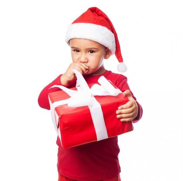 Kid com um presente tocando sua boca