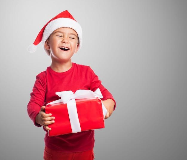 Kid com uma cara engraçada que prende um presente
