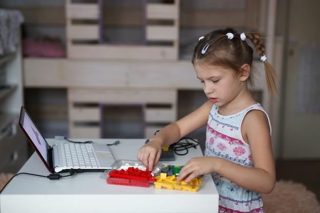 Kid constrói um robô do designer usando laptop