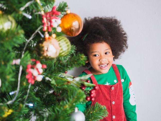 Kid é feliz e engraçado para celebrar o natal com árvore de natal