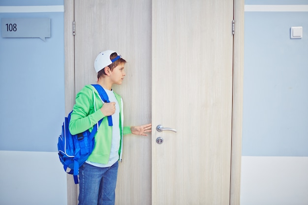 Kid espreita para fora através da porta