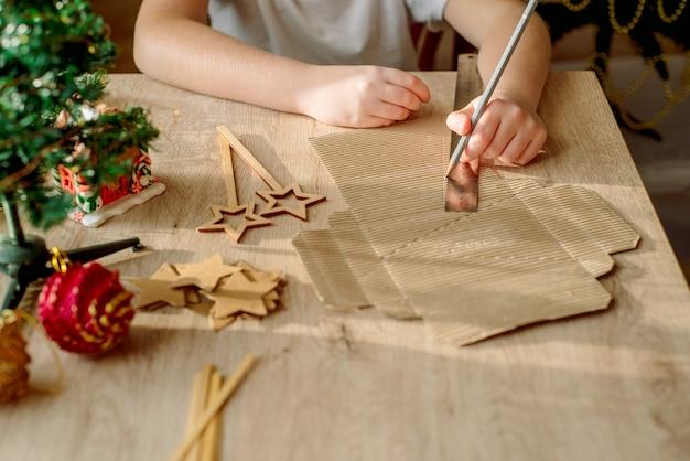 Kid está segurando uma decoração de árvore de natal nas mãos. garoto está mostrando uma decoração de árvore de natal. desperdício zero