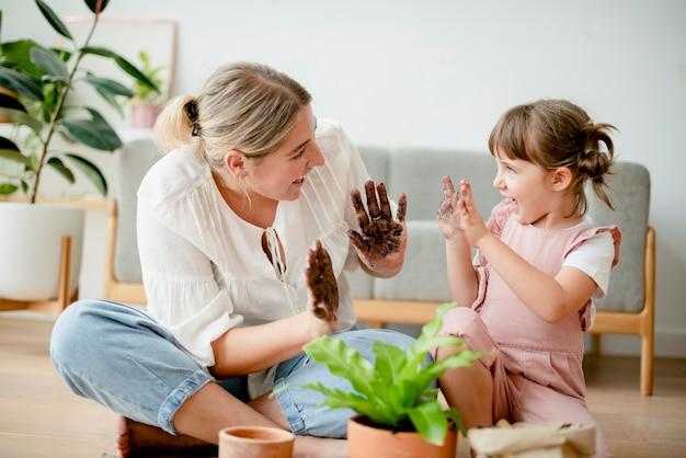 Kid faça você mesmo envasando plantas com a mãe em casa