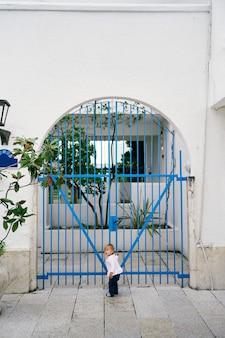 Kid fica no pátio da casa e segura a mão no portão de treliça