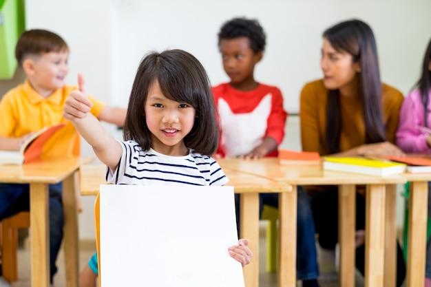 Kid girl thumbs up e segurando cartaz branco em branco com diversidade amigos e professores
