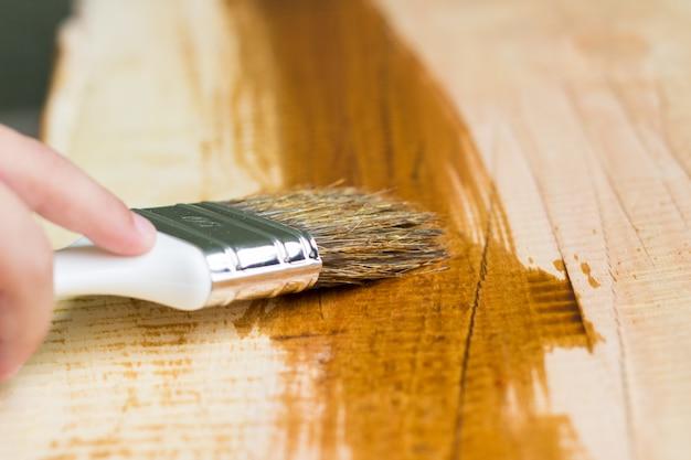 Kid hand varnishing uma prateleira de madeira usando pincel
