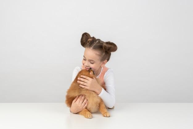 Kid menina playig com cão spitz