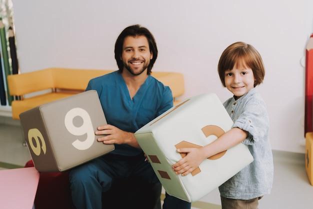 Kid se diverte com o médico no consultório de pediatra