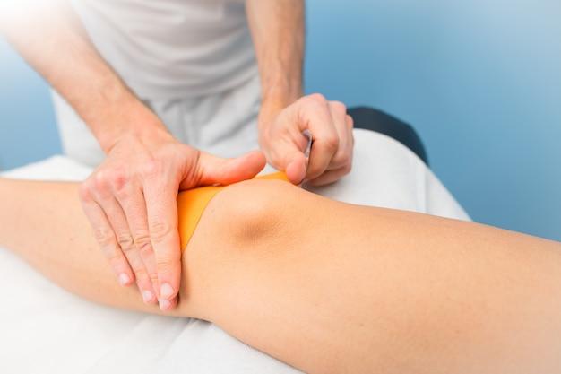 Kinesio gravando aplicação de joelho de fisioterapeuta