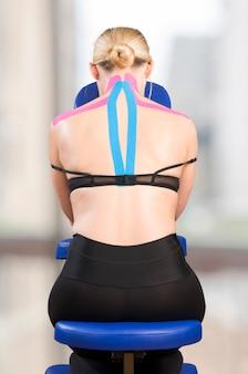 Kinesiotape cor-de-rosa e azul no paciente da mulher. cervical, trapézio, supraespinal, dorsal alto