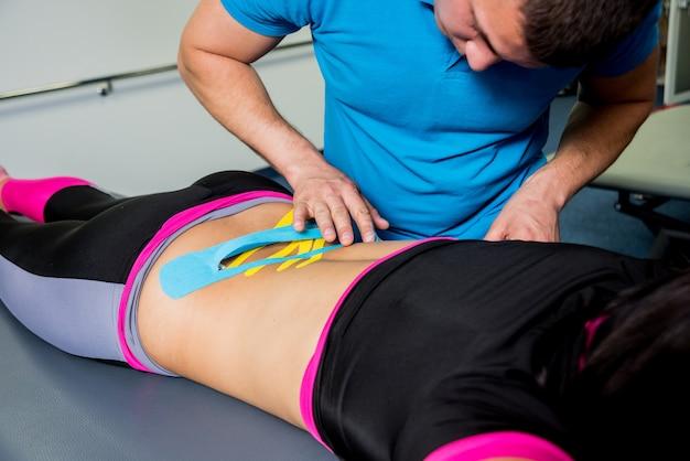 Kinesiotaping. fisioterapeuta aplicar fita na coluna da jovem mulher bonita