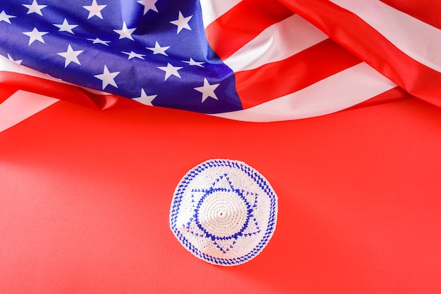 Kipá com a bandeira israelense, ao lado de uma bandeira americana, os estados unidos são um país protetor de israel.