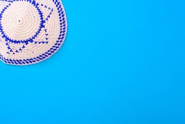Kippah é um chapéu circular, com a bandeira de israel, isolada sobre um fundo azul.