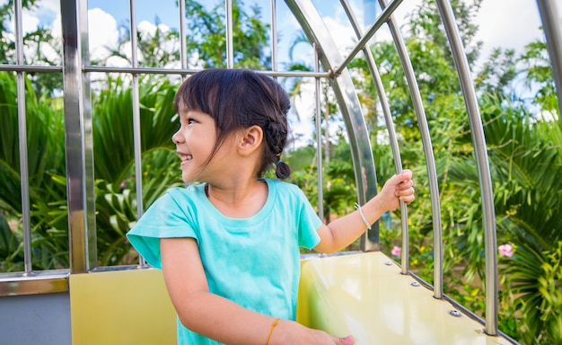 Kit asiático se divertindo em um teleférico de montanha