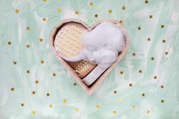 Kit de banho em caixa de madeira em forma de coração na mesa festiva verde com confete de estrelas douradas.
