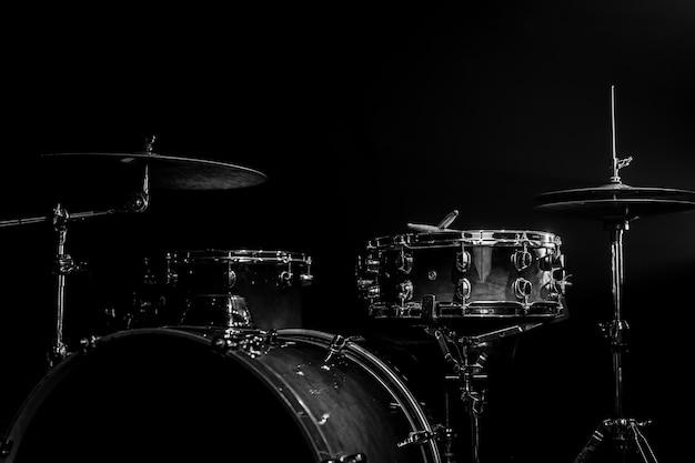 Kit de bateria em um fundo escuro com iluminação de palco, copie o espaço.