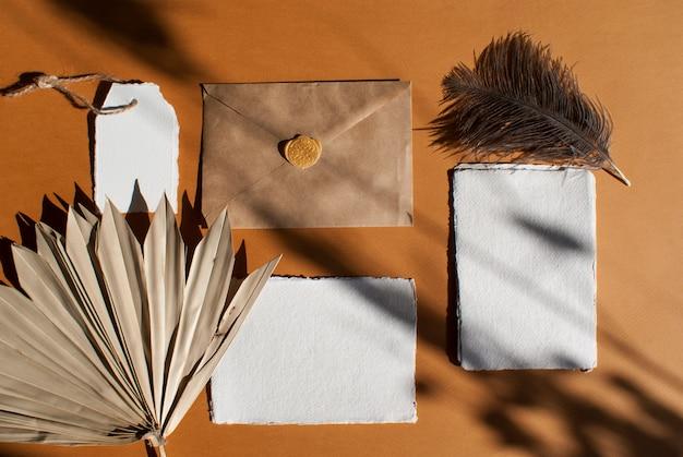 Kit de cartões de convite de papel branco aquarela casamento saudação com folha de palmeira, penas de avestruz, envelope de ofício na mesa de terracota texturizada. elegante modelo moderno. vista plana, vista superior