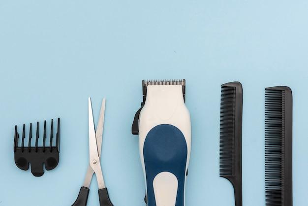 Kit de corte e estilo de cabelo, como pentes, navalha e tesoura dispostos em um fundo azul