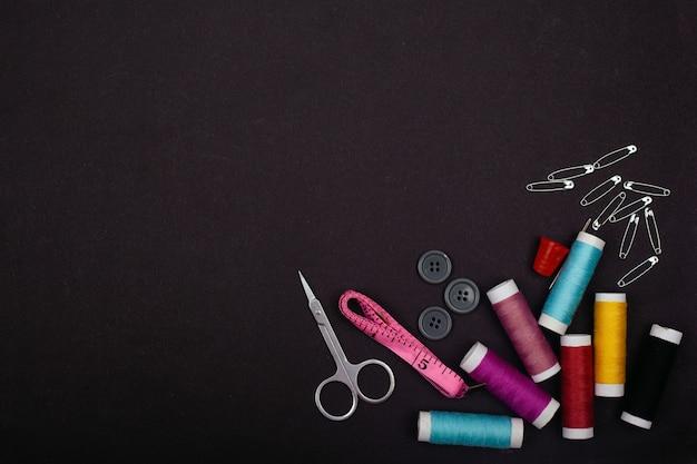 Kit de costura em um fundo preto, linhas, alfinetes, tesouras, espaço de cópia de centímetro.