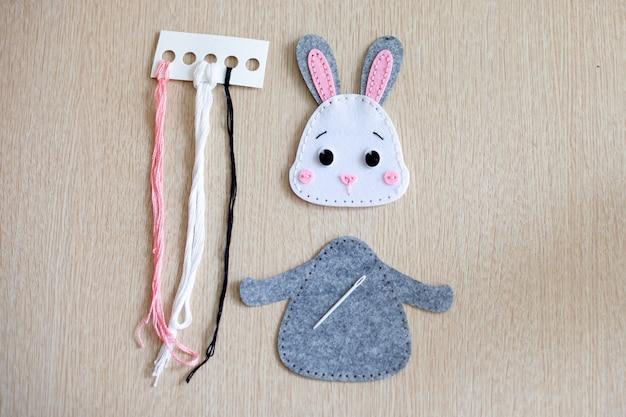 Kit de costura para coelho em feltro: agulha, linha e feltro.