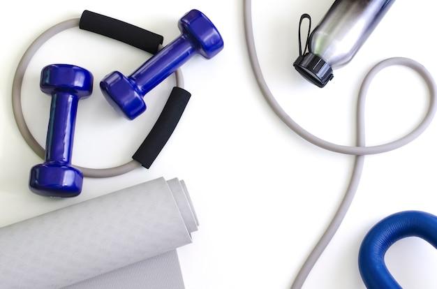 Kit de esportes: halteres, expansor, tapete de ioga, garrafa de água.