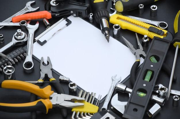 Kit de ferramentas do faz-tudo na mesa de madeira preta com espaço de cópia no tablet de papel em branco.
