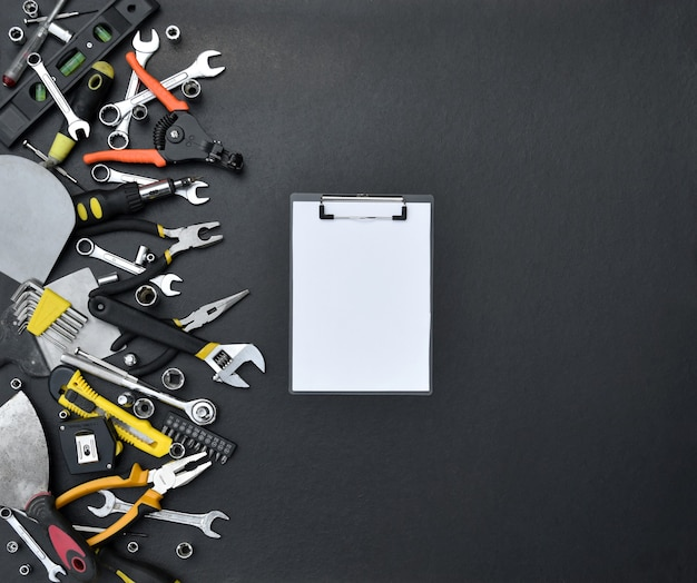 Kit de ferramentas do faz-tudo na mesa de madeira preta. muitas chaves e chaves de fenda, empilhadeiras e outras ferramentas para qualquer tipo de reparo ou construção.