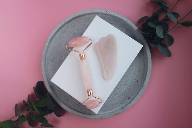Kit de massagem facial. rolo facial e massageador gua sha feito de pedras rosa naturais, bem-estar, conceito de fitness facial, cartão monocromático elegante, banner de luxo.