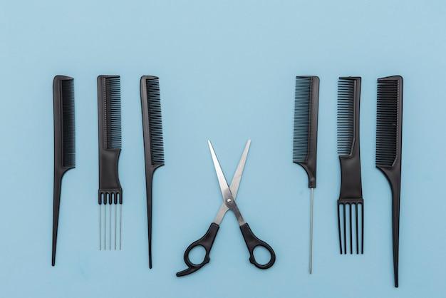 Kit de pentes e tesouras pretas sobre fundo azul