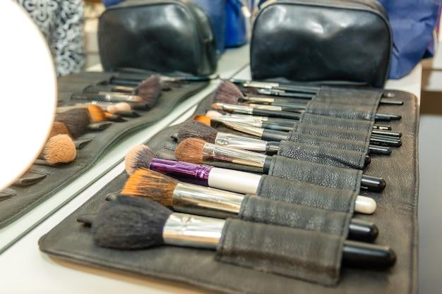 Kit de pincéis de maquiagem com bolsa em soft-foco em segundo plano.