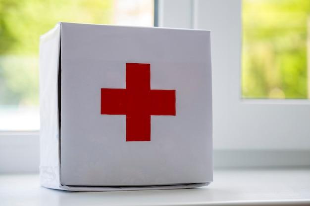 Kit de primeiros socorros branco com cruz vermelha dentro de casa no peitoril da janela no fundo desfocado