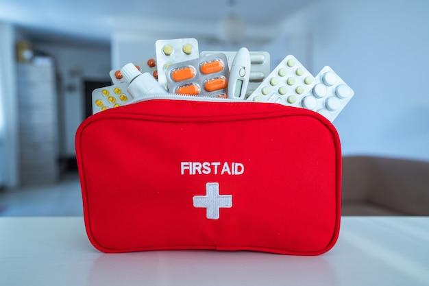 Kit de primeiros socorros com remédios e comprimidos na mesa em casa
