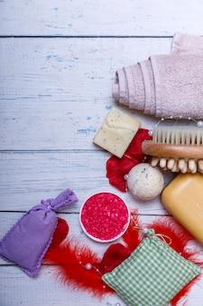 Kit de spa ou definir conceito com produtos orgânicos naturais na mesa de madeira branca. barra de sabão e líquido. sal de aromaterapia rosa. vista superior com espaço de cópia.