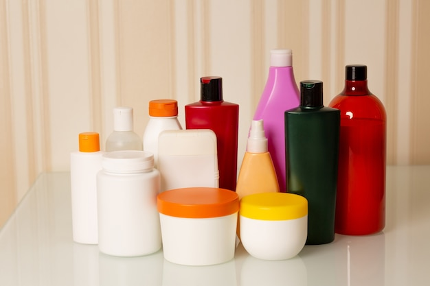 Kit de tratamento capilar: shampoo, condicionador, máscara, óleo e soro sobre fundo bege