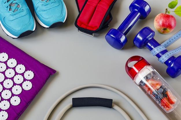 Kit esportivo: halteres, expansor, tênis, água para desintoxicação e tapete de remédios para massagem.