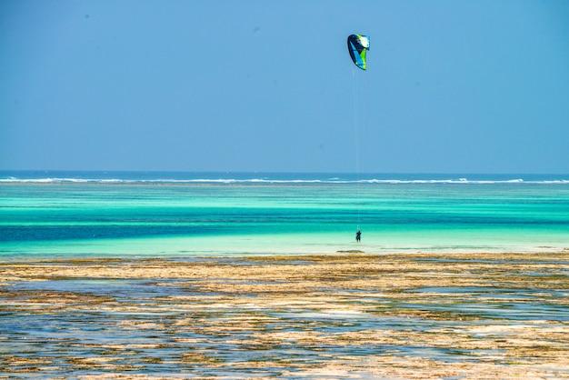 Kitesurfer na maré baixa na praia em zanzibar