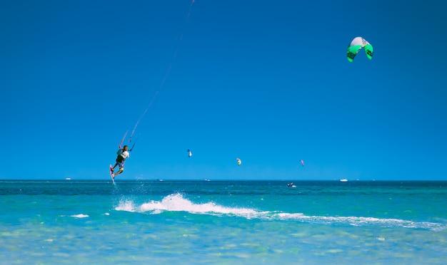 Kitesurfer subindo no céu sobre o mar vermelho