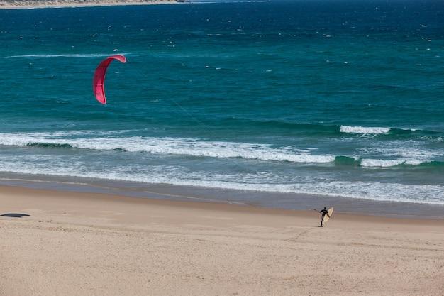 Kitesurfista com kite e prancha de surf indo para o oceano