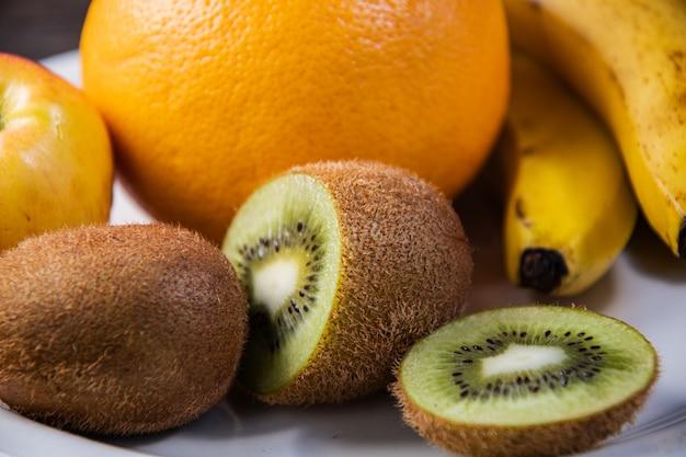 Kiwi, banana, maçã, toranja em um prato branco na mesa da cozinha. cozinhar salada de frutas na cozinha de casa.