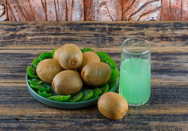 Kiwi com fatias secas, beba em uma bandeja com fundo de madeira, vista de alto ângulo.