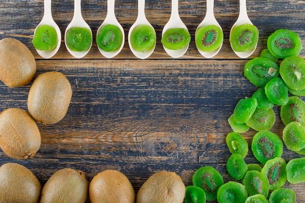 Kiwi com fatias secas estendidas sobre um fundo de madeira