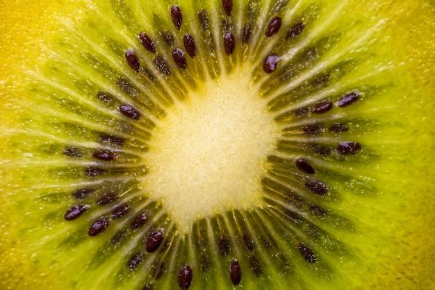 Kiwi com sementes closeup em um corte. macro de fundo verde.