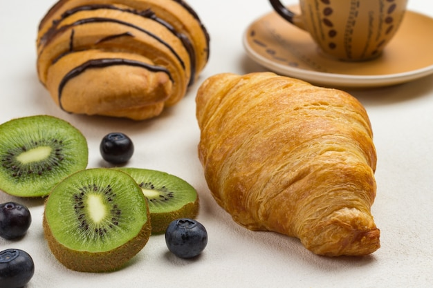 Kiwi e mirtilos, croissant, xícara de café na superfície branca. vista do topo