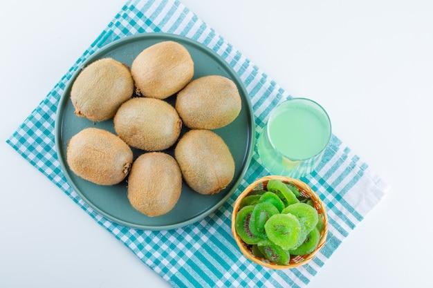 Kiwi em um prato com kiwi seco, bebida deitada no fundo branco e pano de piquenique