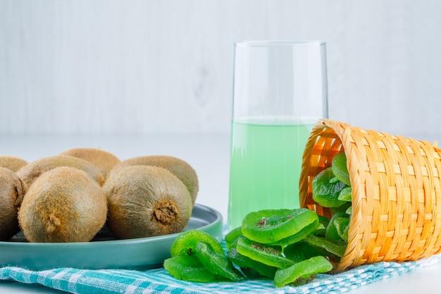 Kiwi em um prato com kiwi seco, vista lateral de bebida no fundo branco e pano de piquenique