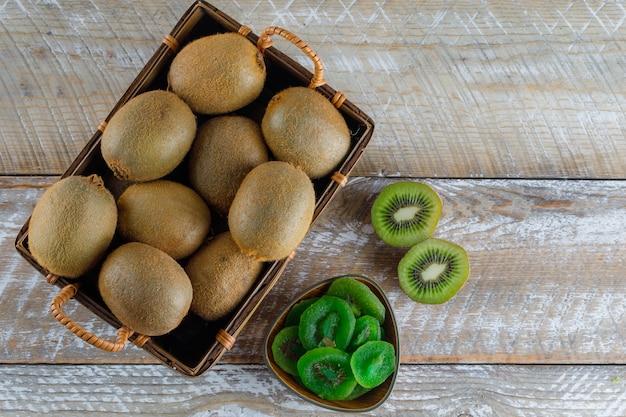 Kiwi em uma cesta com fatias secas planas colocar em uma mesa de madeira