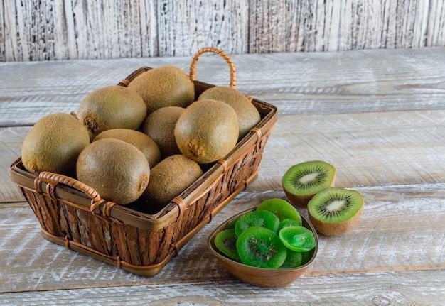 Kiwi em uma cesta com fatias secas, vista de alto ângulo sobre uma mesa de madeira