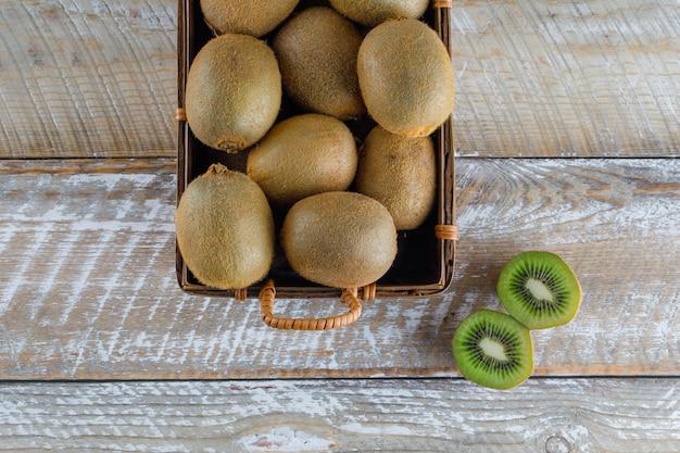 Kiwi em uma cesta plana estava em uma mesa de madeira