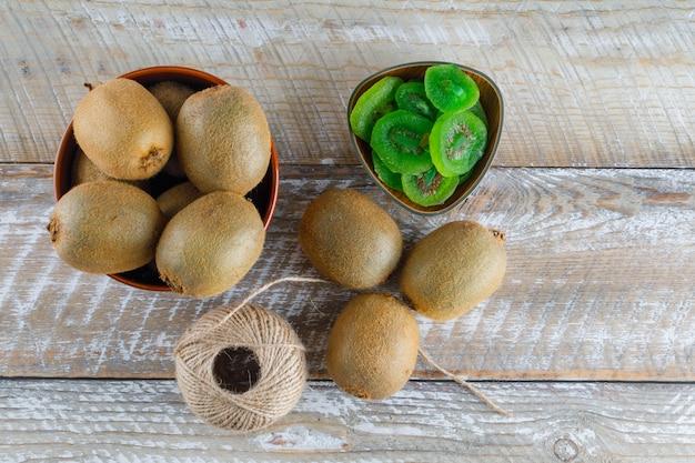 Kiwi em uma tigela com fatias secas, bola de fio plana colocar em uma mesa de madeira