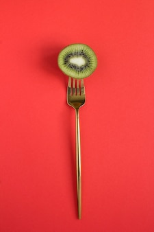 Kiwi fatiado empalado em um garfo de ouro